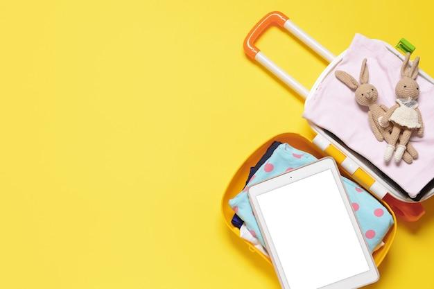 Walizka Z Akcesoriami Podróżnymi Dla Dzieci I Tabletem Na Kolorowej Powierzchni Premium Zdjęcia