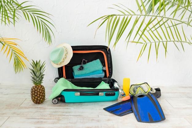 Walizka z letnimi rzeczami na wakacje, pojęcie podróży i lata