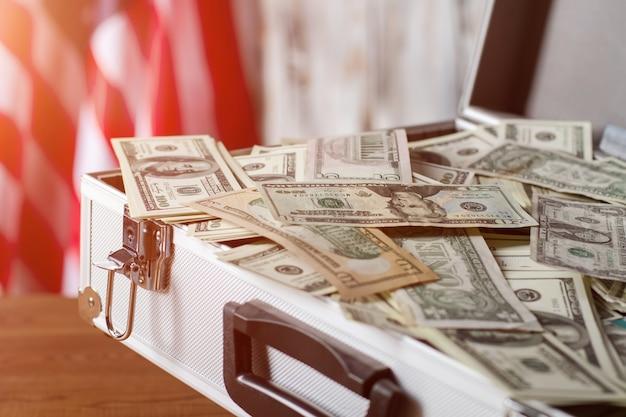 Walizka ze stosem dolarów. amerykańska flaga w pobliżu dużych pieniędzy. zysk taki jaki jest. życie daje ci możliwości.