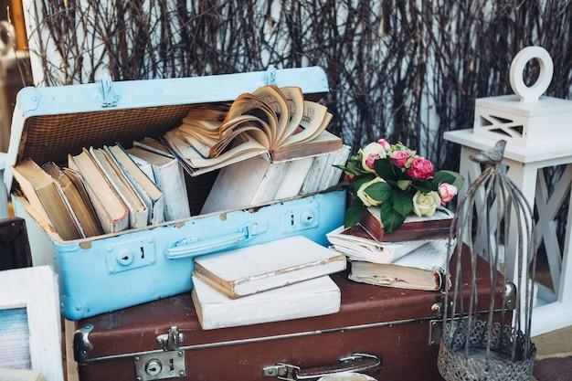 Walizki z książkami i kwiatami na stole