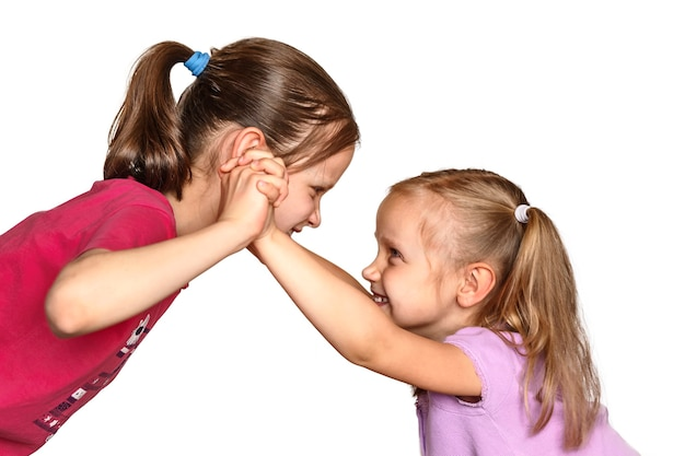 Walka między dwiema małymi dziewczynkami dzieci bawiące się na białym tle