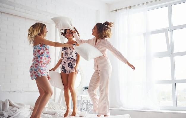 Walka na poduszki. szczęśliwe koleżanki dobrze się bawią na imprezie piżamy w sypialni.
