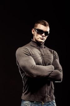 Walka z umięśnionym bohaterem człowieka na sobie brązowy sweter i okulary przeciwsłoneczne