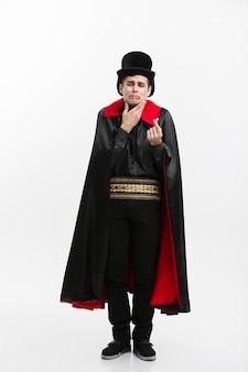 Wampir halloween concept - portret przystojny wampir kaukaski raniąc się ząb wampira.