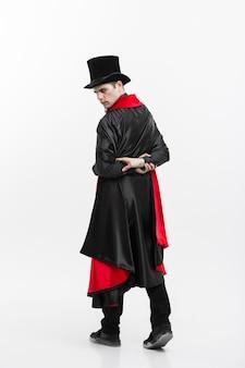 Wampir halloween koncepcja - portret przystojny wampir kaukaski trzymając czerwoną piękną różę.