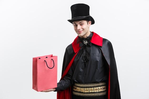 Wampir halloween koncepcja - szczęśliwy przystojny wampir kaukaski trzymając kolorową torbę na zakupy na białej ścianie.