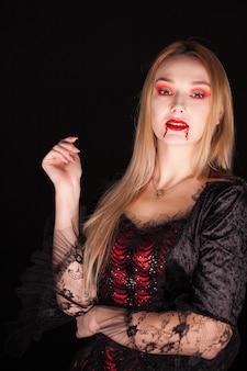 Wampir piękna kobieta z krwawymi ustami na czarnym tle. kostium na halloween.