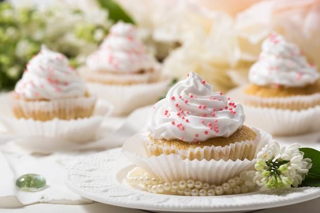 Waniliowe babeczki z białą śmietaną na białym stole, białym kwiacie i liściu