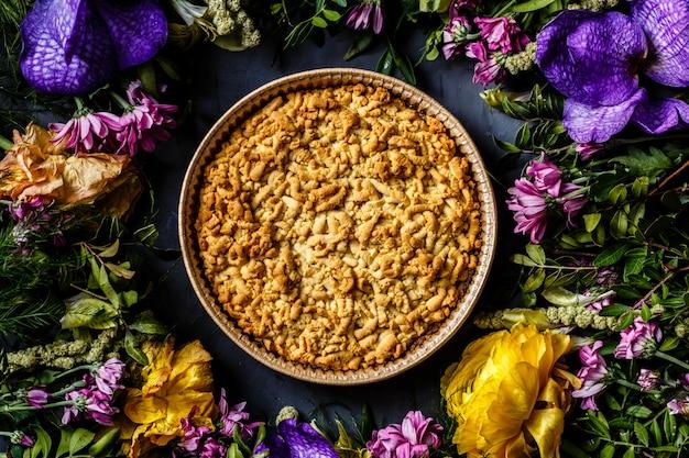 Waniliowy jabłecznik deser i jasne kwiaty na szarym tle.