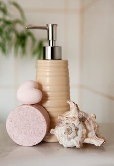 Wanna ceramiczna butelka, mydło, muszla i bomba do kąpieli na niewyraźne tło wnętrza łazienki z umywalką