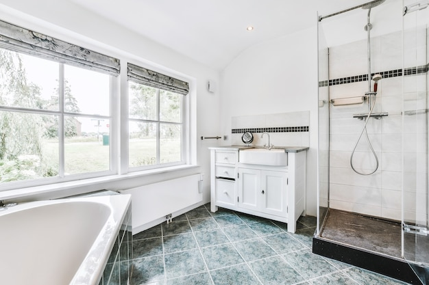 Wanna i kabina prysznicowa na wyłożonej kafelkami ścianie obok szafki ze zlewem przy oknie w domu