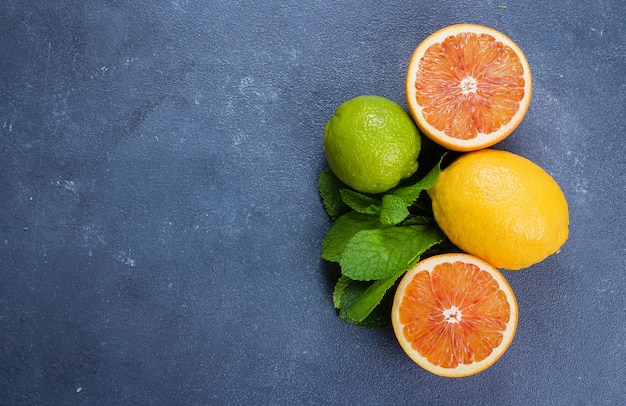 Wapna, cytryny i czerwieni pomarańcze na błękitnym stonebackground. składniki na mojito lub lemoniadę