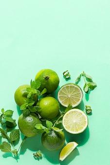 Wapna i mięta w słońcu z cieniem na tle zielonej księgi. koncepcja żywności. widok z góry z miejscem na kopię.