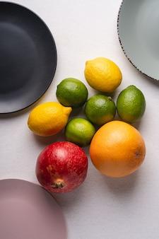 Wapno, cytryna, grejpfrut i granat z pustymi talerzami na białym tle