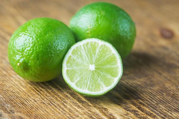 Wapno owocowe z plastrami limonki na drewnie. owoc cytrusowy.