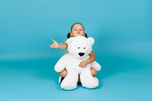 Warkocze dziecko siedzi ze skrzyżowanymi nogami na podłodze, przytula białego misia i przesyła buziaka