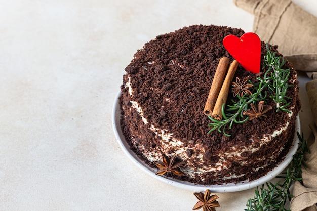 Warstwowe ciasto czekoladowe ozdobione sercem, rozmarynem, cynamonem i anyżem