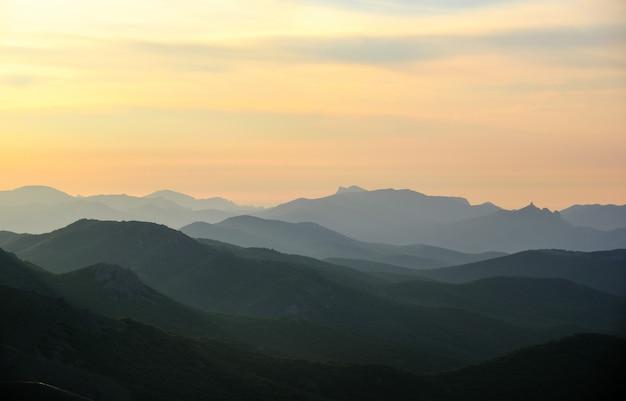 Warstwowe góry w mgle na słońcu. wschód słońca w górach krymskich.