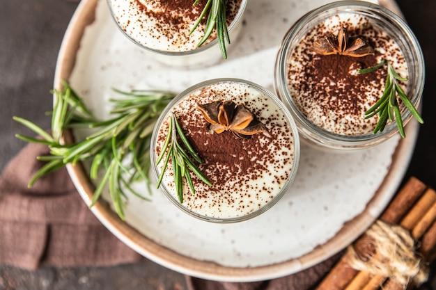 Warstwowy deser w szklanym słoju z kruszonką i bitą śmietaną ozdobiony rozmarynem i anyżem, powierzchnia ciemnobrązowa
