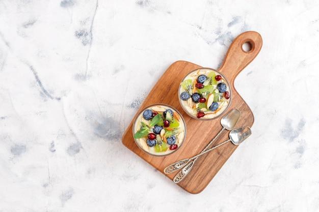 Warstwowy drobiazgowy deser w szklankach do serwowania.
