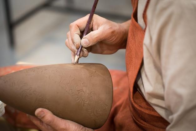 Warsztat ceramiczny, mistrz stawia na nie wypalony dzban ceramiczny