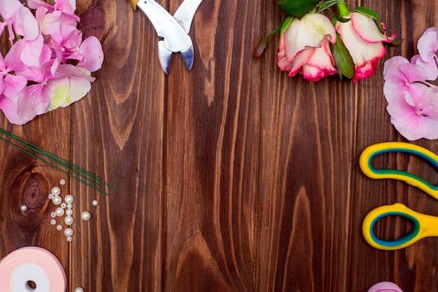 Warsztat kwiaciarni. narzędzia: nożyczki, sekator na tle stołu z kwiatami. twórz kompozycje kwiatowe na dzień matki lub walentynki