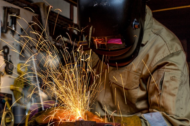 Warsztat spawacza szkolący fabrycznie spawalniczy metal z maską ochronną, mundurem i rękawicą