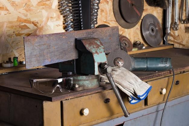 Warsztat warsztatowy z mistrzem ślusarskim miejsce pracy okulary ochronne maszyna do cięcia rękawic