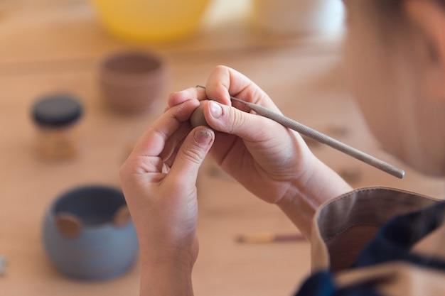 Warsztaty garncarskie dla dzieci dziewczyna pracująca z glinianymi rękami zbliżenie