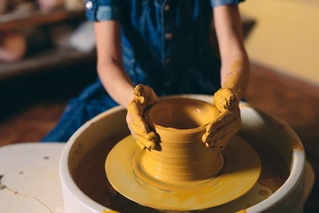 Warsztaty garncarskie. mała dziewczynka robi wazon z gliny. modelowanie gliny