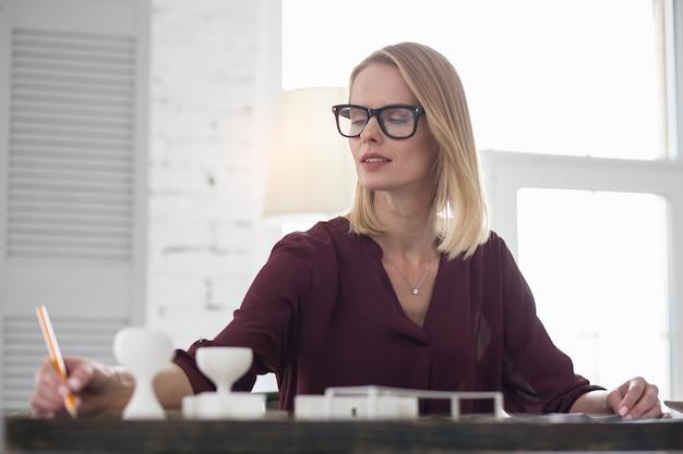 Warto zauważyć. zamyślona projektantka robi notatki i nosi okulary