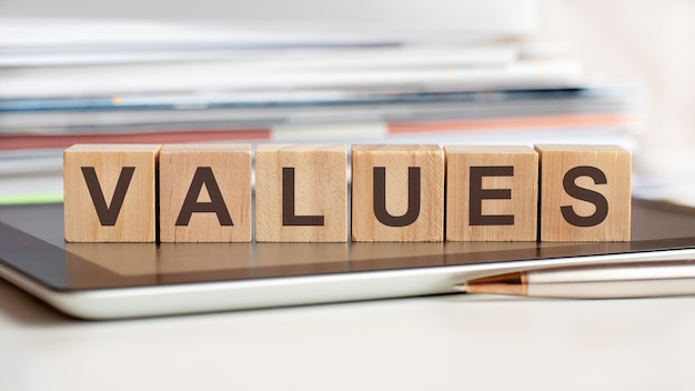Wartości słów są zapisane na drewnianych kostkach stojących na notatniku. może służyć do biznesu, edukacji, koncepcji finansowej.