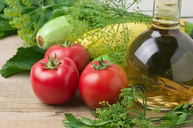 Warzywa i butelka oleju, martwa natura na drewnianym stole