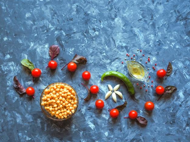 Warzywa i ciecierzyca pięknie ułożone na ciemnym stole
