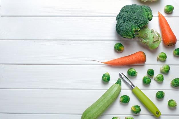 Warzywa i obieraczka na białym drewnie