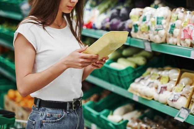 Warzywa i owoce. kobieta kupująca w zwykłych ubraniach na rynku, szukająca produktów.