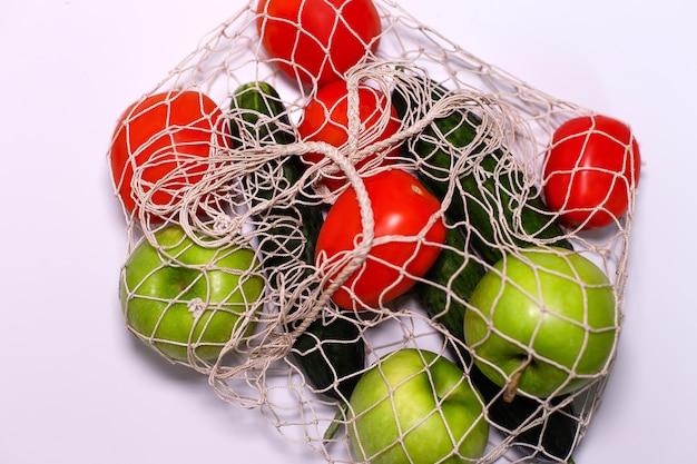 Warzywa i owoce w siatce na szarej ścianie