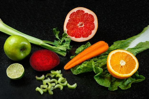 Warzywa i owoce zdrowa żywność wypadają na ciemnym stole. świeża pomarańcza, jabłko, limonka, marchewka, surówka, burak i seler.
