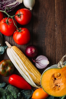 Warzywa i pomidory na drewnianej kopii przestrzeni tle