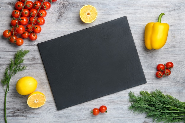 Warzywa i pusta kamienna rama na drewnianym stole. tło dla receptury żywności i koncepcji gotowania. widok z góry