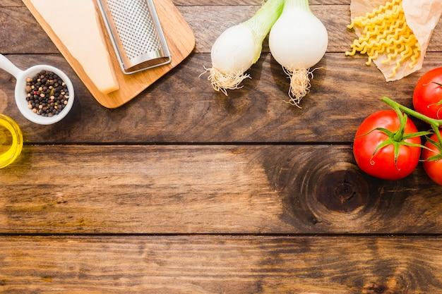 Warzywa i ser w pobliżu makaronu i przypraw