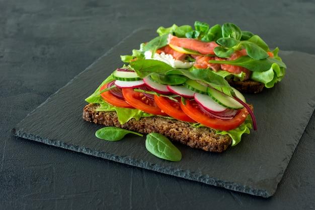 Warzywa i wędzone otwarte kanapki z twarogiem, kratą, pomidorami i cytryną na łupku