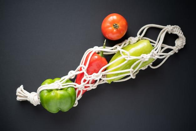Warzywa i zielenie w sznurkowej torbie na ciemnym tle widok z góry