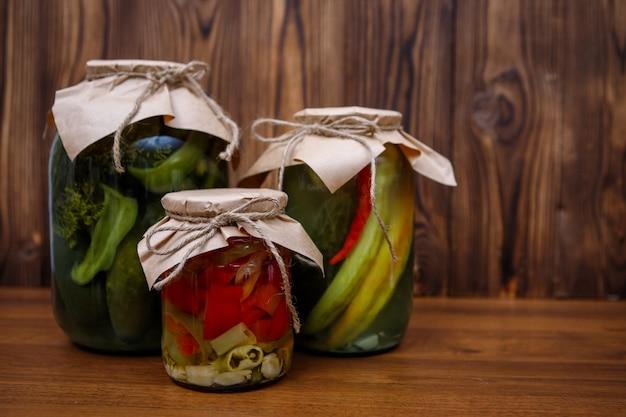 Warzywa konserwowane w szklanych słoikach na drewnie
