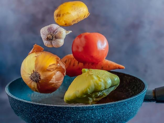 Warzywa lewitujące nad patelnią na gulasz warzywny. koncepcja gotowania.