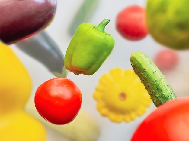 Warzywa lewitujące w powietrzu papryka, ogórek, cukinia, bakłażan i pomidor na białym tle. koncepcja zdrowej żywności