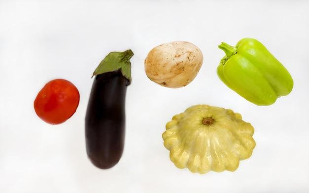 Warzywa lewitujące w powietrzu papryka, ziemniaki, cukinia, bakłażan i pomidor na białym tle. koncepcja zdrowej żywności.