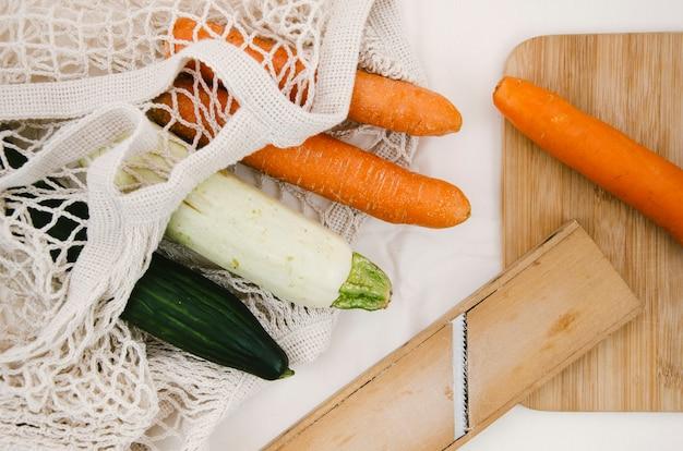 Warzywa leżące płasko w szydełkowej torbie z siatki