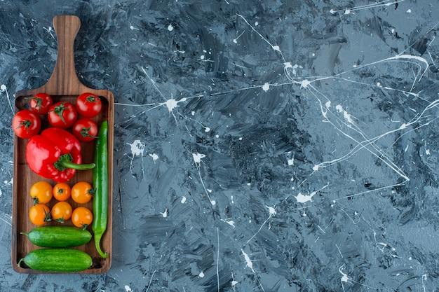 Warzywa mieszane na desce, na tle marmuru.