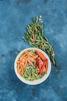 Warzywa mrożone: meksykańska mieszanka warzyw na głębokim białym talerzu z fasolką szparagową na niebieskim tle.